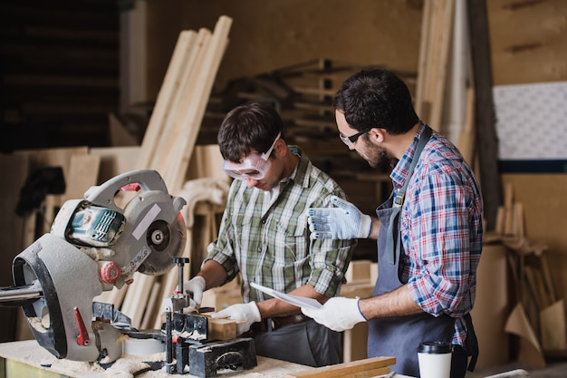 Inspetor e carpinteiro discutem o processo de fabricação de produtos de madeira para móveis
