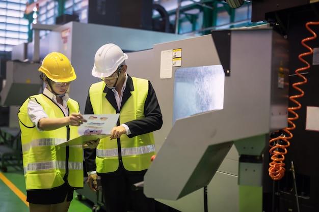 Inspetor e gerente de fábrica verificam o modelo do produto