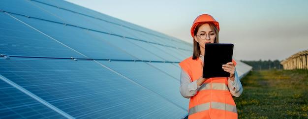 Inspetor engenheiro mulher segurando tablet digital trabalhando em painéis solares power farm, parque de células fotovoltaicas, conceito de energia verde.