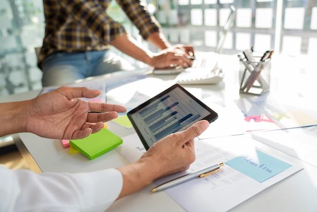 Inspetor financeiro de homem de negócios e secretário fazendo relatório e brainstorming com o colega em um espaço moderno de co-working.