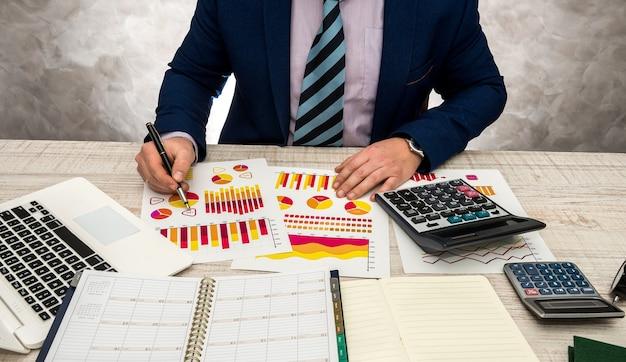 Inspetor financeiro fazendo relatório relatório de planejamento financeiro usando papel gráfico e laptop para receita ou orçamento de venda neste ano.
