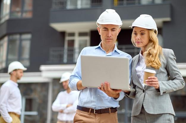 Inspetor focado e seu colega com um laptop ao ar livre
