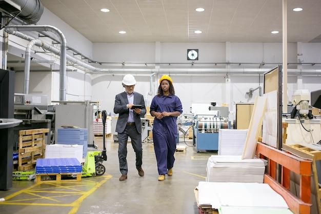 Inspetor masculino sério e funcionária da fábrica em capacetes, caminhando no chão da fábrica e conversando, homem usando tablet
