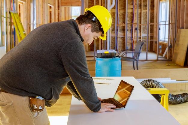 Inspetor na casa de construção nova com tablet fazendo anotações