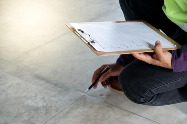 Inspetor ou engenheiro está verificando e inspecionando a aparência do piso e apontando para a superfície