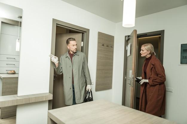 Inspetor resoluto. detetive vestindo capa de chuva e perguntando sobre a segurança da próxima sala, trabalhando cuidadosamente no novo lugar