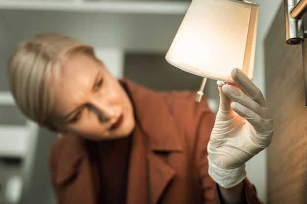 Inspetor revisando o interior. detetive loiro sério usando luvas de borracha durante a operação sendo surpreendido pelo microfone