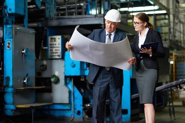 Inspetor sênior, olhando para os planos de fábrica