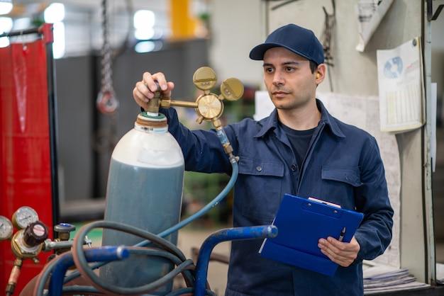 Inspetor verificando um tanque de gás em uma fábrica industrial