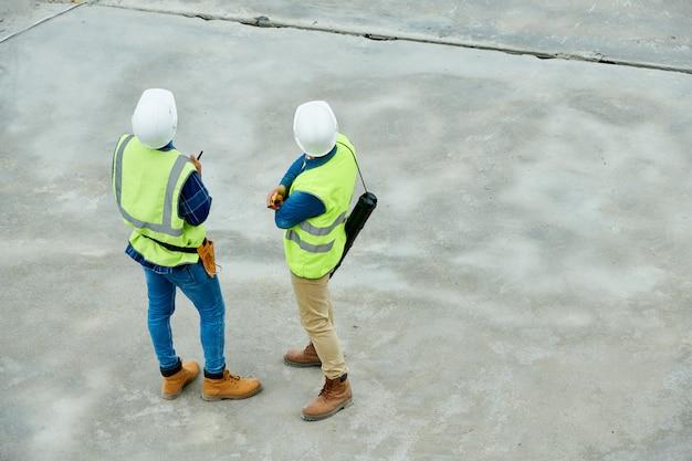 Inspetores de construção irreconhecíveis no canteiro de obras