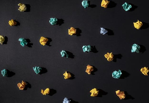 Inspiração de criatividade, conceitos de ideias com bola amassada de papel sobre fundo de cor preta. projeto liso leigo.