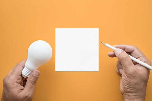 Inspiração de criatividade idéias conceitos com lâmpada e bloco de notas em pastel