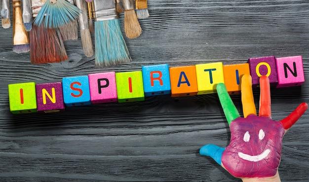 Inspiração de palavras com pincéis e mão humana em fundo de madeira