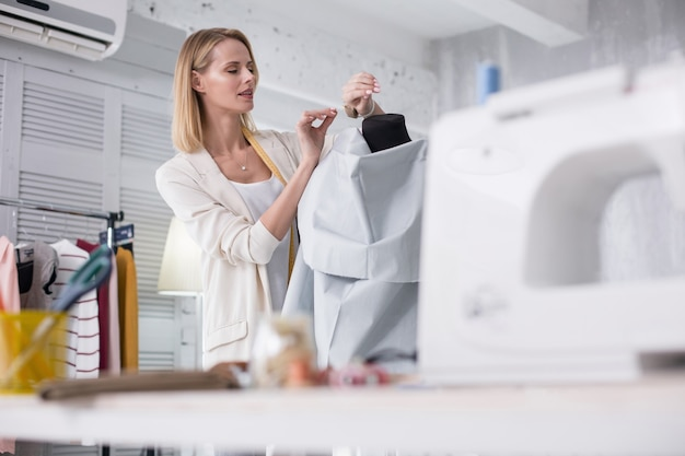 Inspiração de trabalho. alfaiate feminina atraente pegando alfinete enquanto olha para baixo