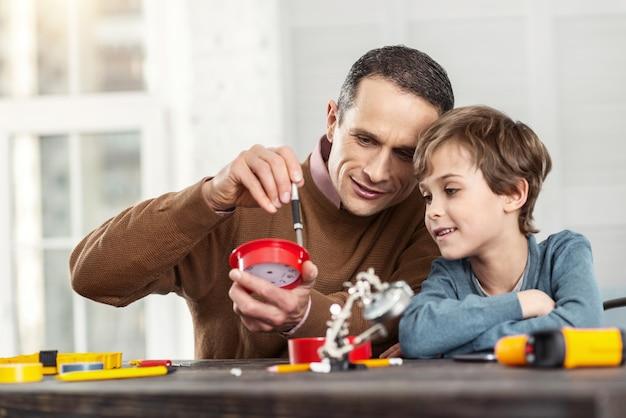 Inspiração. homem bonito e alerta de cabelos escuros mostrando instrumentos para o filho enquanto está sentado na mesa e o ensinando