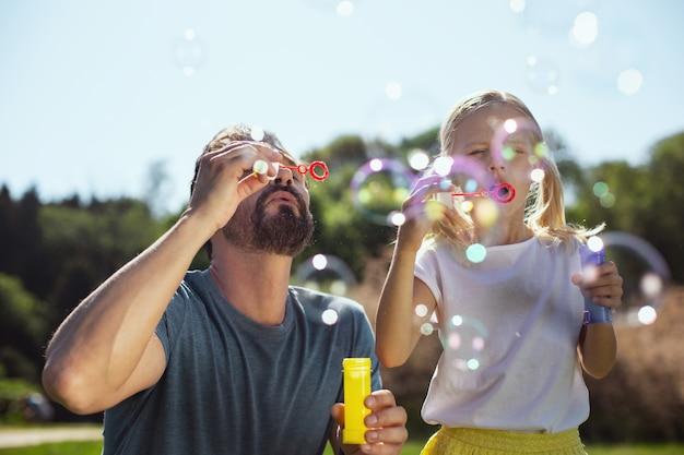 Inspiração. pai barbudo amoroso soprando bolhas de sabão com a filha enquanto relaxa no parque