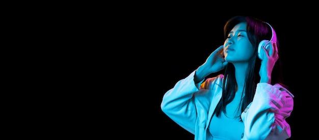 Inspiração. retrato de mulher jovem asiática na parede escura em luz de néon. bela modelo feminino com fones de ouvido. conceito de emoções humanas, expressão facial, juventude, vendas, anúncio.