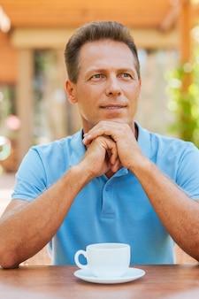 Inspirado com uma xícara de café fresco. homem maduro pensativo de mãos dadas no queixo enquanto está sentado na calçada de um café com uma xícara de café na mesa