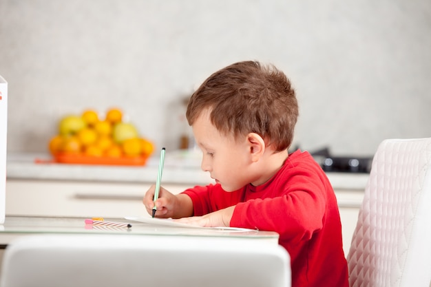 Inspirado pelo menino, desenha uma imagem no papel à mesa