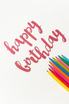 Inspiradora frase 'feliz aniversário' para cartões e cartazes de desenho com marcador vermelho sobre papel branco. vista superior das letras, monte de marcadores coloridos