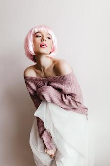 Inspiradora jovem europeia em exuberante saia branca sonhadora olhando para longe. senhora bonita no peruke da moda.