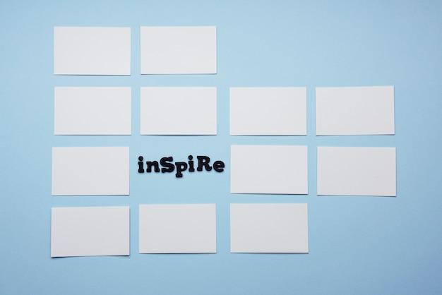 Inspirar a palavra rodeada por cartões de visita vazios vista superior