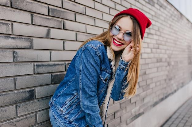 Inspirou garota europeia em jeans da moda posando perto da parede de tijolos. foto ao ar livre da senhora loira feliz tocando seus óculos azuis.