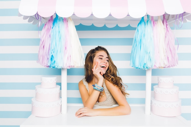 Inspirou uma linda garota de cabelos compridos em acessórios azuis da moda, sentada atrás do balcão com sobremesas na parede listrada. encantadora vendedora feliz rindo, posando na loja de doces com os olhos fechados.