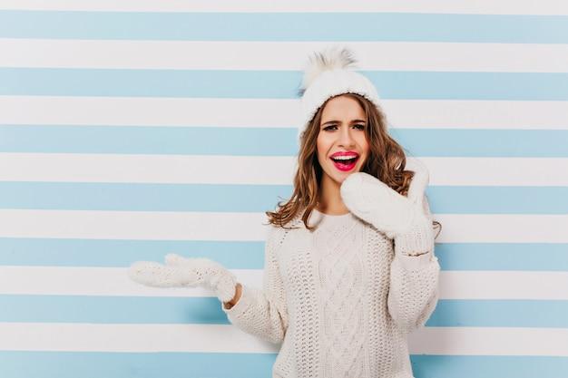 Inspirou uma mulher europeia de cabelos escuros em um lindo suéter branco posando. modelo feminino sonhador em roupas de inverno de lã em pé na parede listrada de luz.