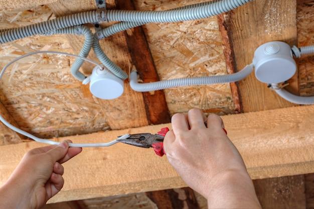 Instalação da fiação elétrica no teto, mãos do eletricista com alicate, close-up.