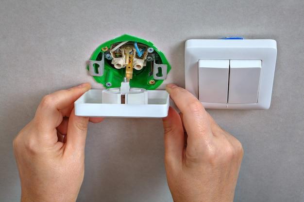 Instalação da tomada na caixa de montagem, close-up do eletricista nas mãos.