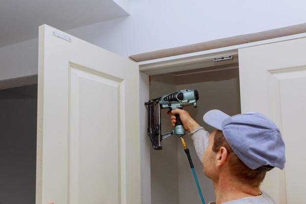 Instalação das portas interiores dos quartos usando uma pistola de pregos