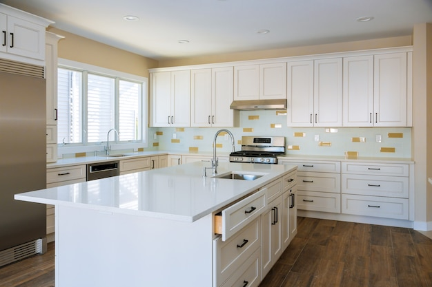 Instalação de armários e bancada de uma cozinha branca parcialmente móveis instalados.