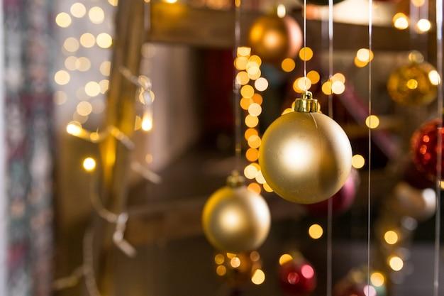Instalação de arte de árvore de natal feita com luzes de corda e bolas de natal penduradas em fios