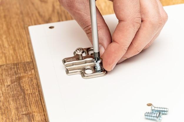 Instalação de dobradiças de portas de móveis, acessórios, processo de montagem de móveis com chave de fenda