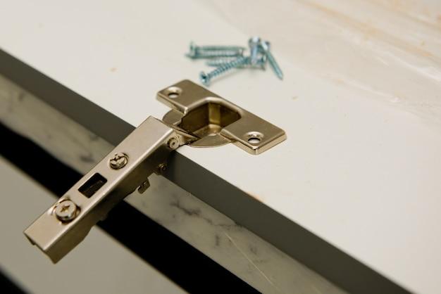 Instalação de dobradiças metálicas no cartão. foco seletivo. fechar-se.