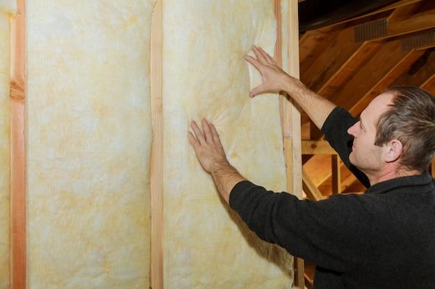 Instalação de isolamento de parede interior em casa de madeira, edifício em construção