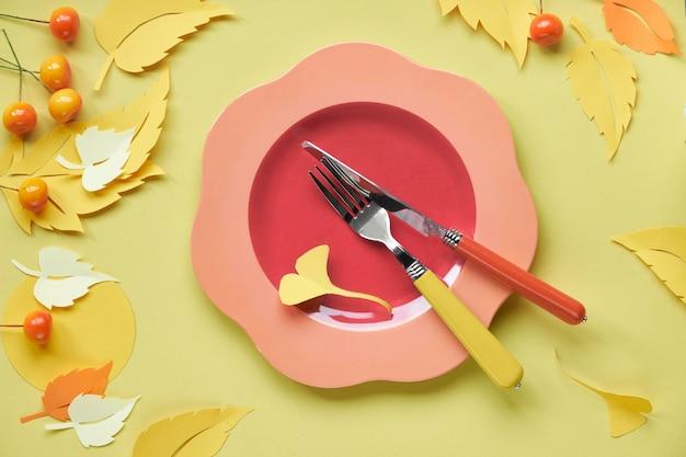 Instalação de mesa para a celebração do outono. prato de plástico brilhante em papel amarelo com folhas de outono de papel