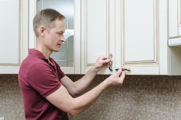 Instalação de móveis de cozinha com o homem colocando as maçanetas nos armários das portas