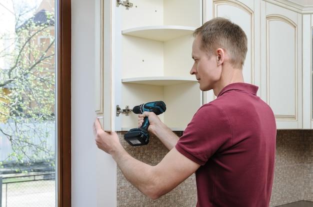 Instalação de móveis de cozinha com o homem usando uma chave de fenda