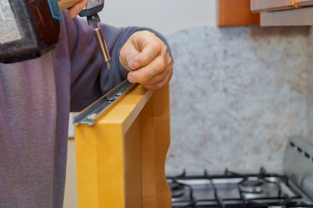 Instalação de móveis de cozinha. gaveta de prateleira de montagem