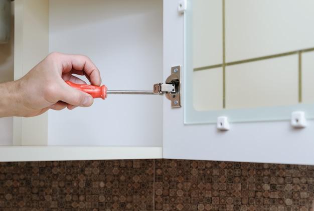 Instalação de móveis de cozinha utilizando uma chave de fenda para ajustar a porta do armário
