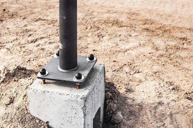 Instalação de postes de iluminação em base de concreto. eletrificação da cidade. obras de construção em quarteirão.