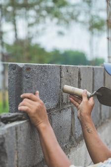 Instalação de tijolos de cimento no canteiro de obras