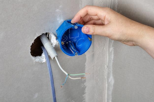 Instalação de tomada elétrica, mãos de eletricista instalando caixa de tomada de plástico para tomadas elétricas.