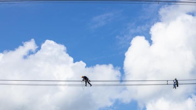 Instalação de trabalho de eletricista de cabo de alta tensão em alta tensão com segurança