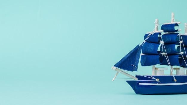 Instalação de um veleiro flutuando lateralmente sobre uma superfície azul. o conceito de viagem e aventura.