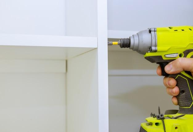 Instalação de uma chave de fenda nas prateleiras de madeira na parede