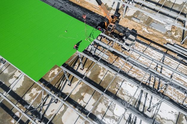 Instalação de uma folha de perfil no telhado de um edifício industrial