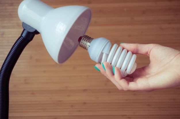 Instalação de uma lâmpada econômica moderna em um candeeiro de mesa
